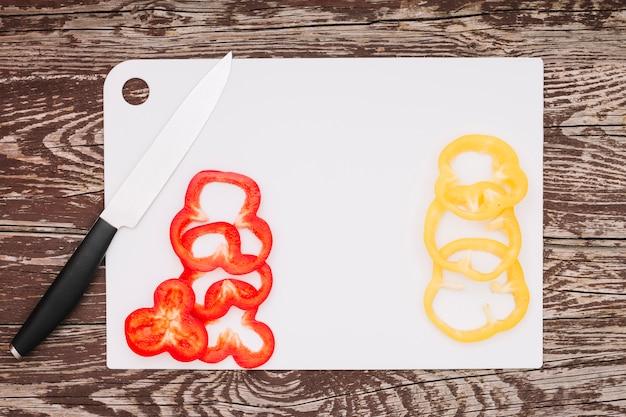 Rebanadas de pimiento rojo y amarillo en la tajadera blanca sobre el fondo de madera de la textura