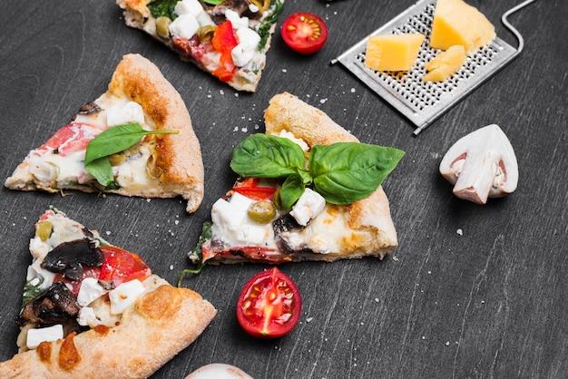 Rebanadas de pizza de alto ángulo con tomates