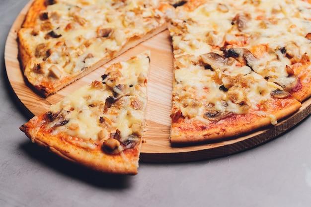 Rebanadas de pizza en bandeja de madera rústica y fondo oscuro.