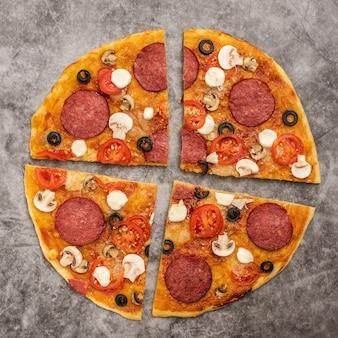 Rebanadas de pizza italiana con queso, mozzarella, champiñones y salami sobre gris. vista superior.