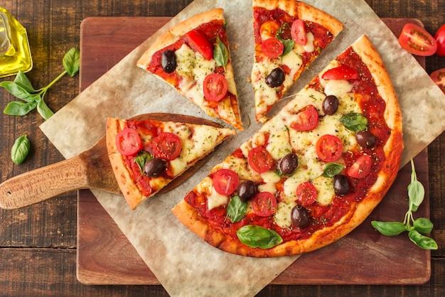 Rebanadas de pizza en mármol sobre la tabla de cortar