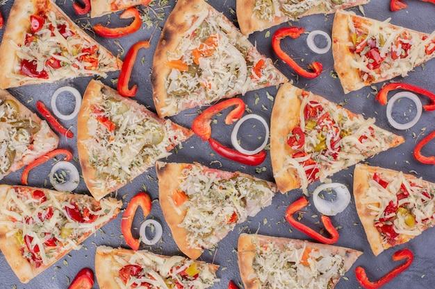 Rebanadas de pizza sabrosa en azul con aros de cebolla y pimiento.