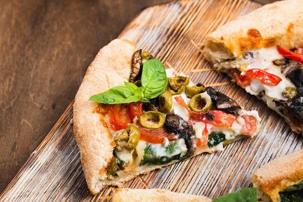 Rebanadas de pizza en la tabla de cortar alto ángulo