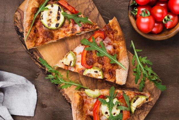 Rebanadas de pizza en tablero de madera plano lay