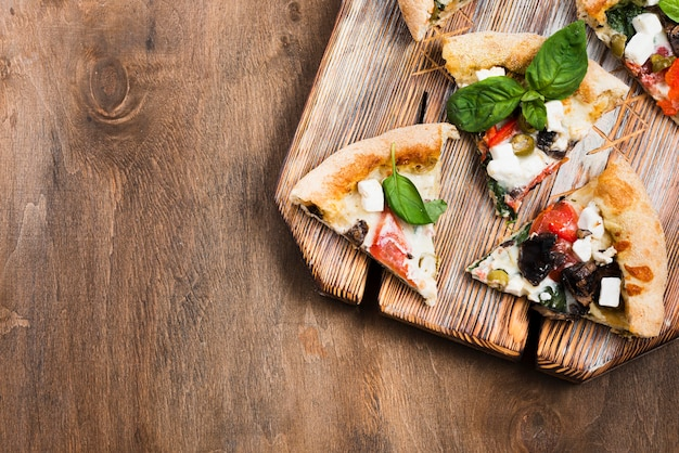 Rebanadas de pizza en la vista superior de la tabla de cortar