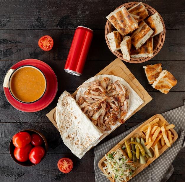 Rebanadas de pollo donado en pan plano, servido con sopa de lentejas y guarniciones