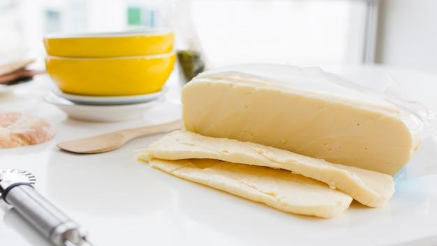 Rebanadas de queso cheddar en escritorio blanco con tazones