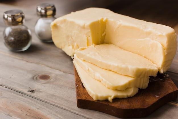 Rebanadas de queso cheddar en la tabla de cortar con salero y pimentero en la mesa