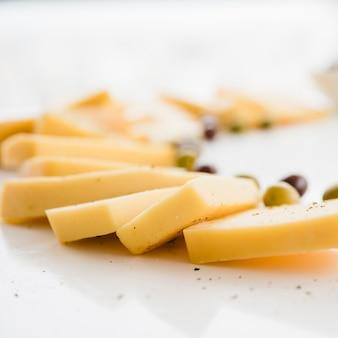 Rebanadas de queso delicioso fresco con aceitunas en escritorio blanco