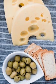 Rebanadas de queso emmental; pan y aceitunas frescas en mantel.
