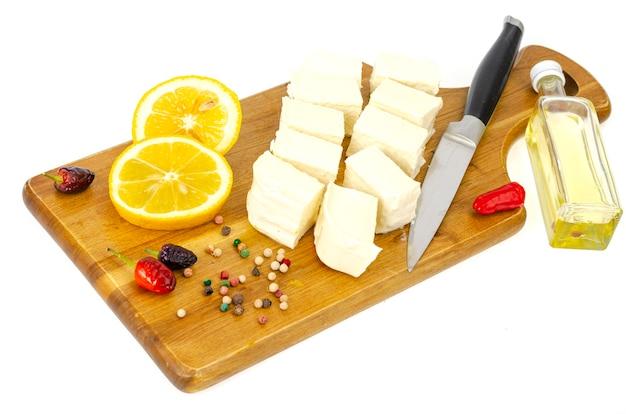 Rebanadas de queso feta blanco fresco sobre tabla de cortar de madera.