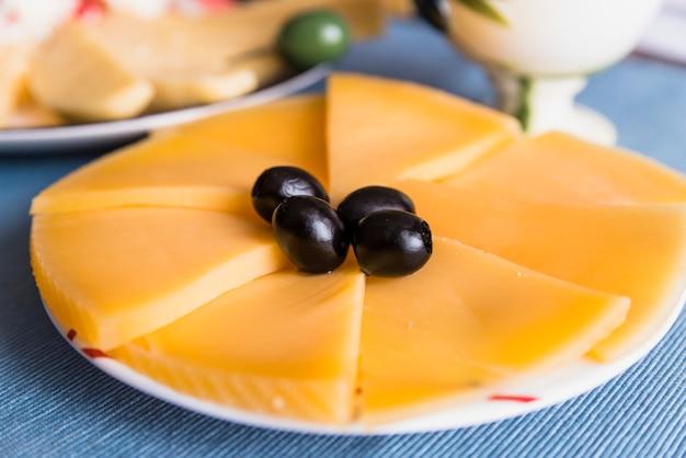 Rebanadas de queso fresco con aceitunas sabrosas en placa