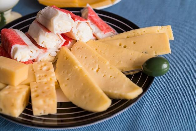 Rebanadas de queso fresco cerca de bocadillos y selección en plato