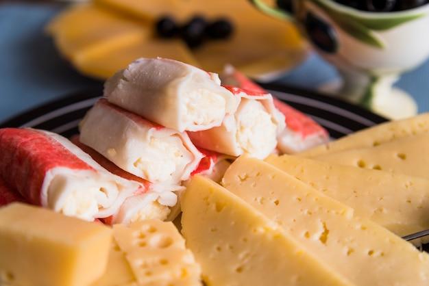 Rebanadas de queso fresco cerca de sabrosos aperitivos en un plato