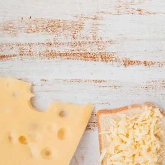 Rebanadas y queso rallado emmental sobre mesa de madera.