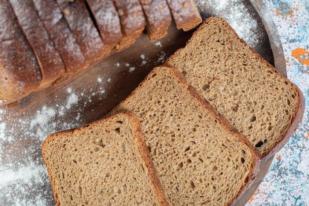 Rebanadas de rebanadas de pan integral en placa de madera.