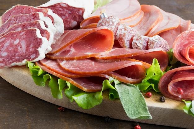 Rebanadas de salami francés secado con queso y especias sobre fondo de madera