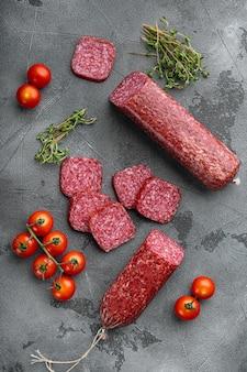 Rebanadas de salami con verduras, sobre fondo de mesa de piedra gris, vista superior plana