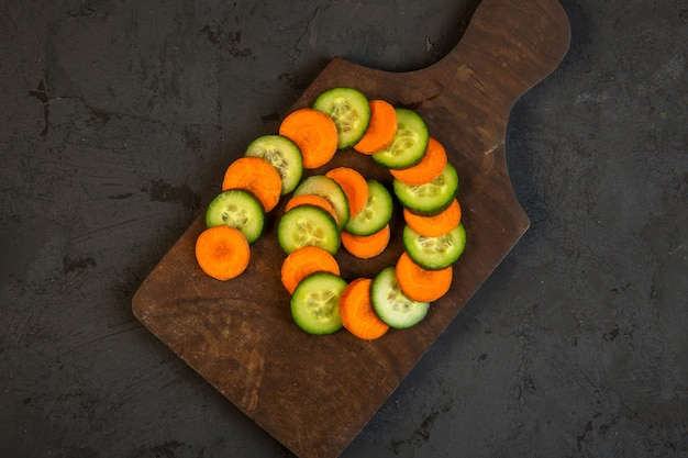Rebanadas superiores de zanahoria y pepino en tabla de cortar de madera en negro