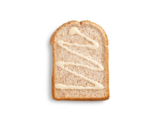 Rebanar pan integral con leche condensada azucarada sobre fondo blanco.