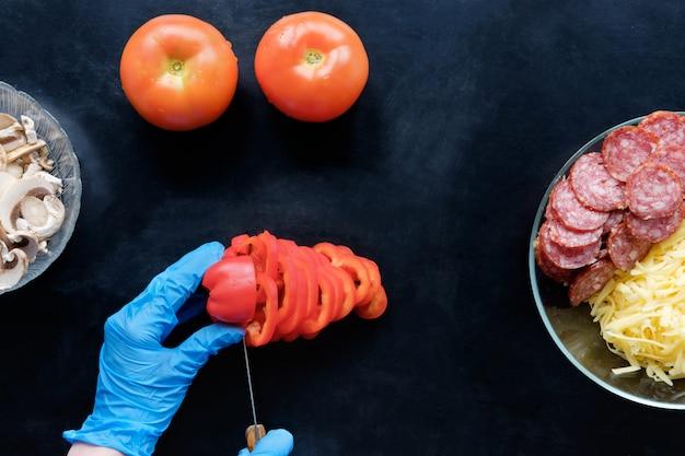 Rebanar tomate e ingredientes en la cocina, vista superior