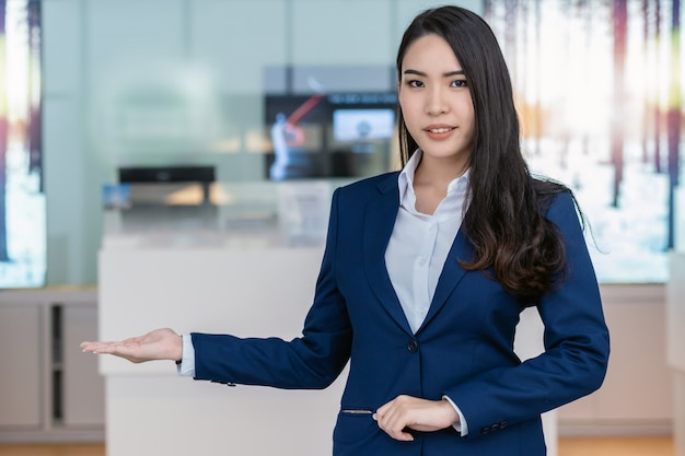 Recepción asiática que da la bienvenida al cliente al mostrador de la sala de exhibición de automóviles para el servicio al cliente.