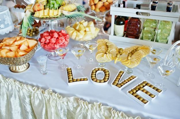 Recepción de bodas con dulces, bebidas y frutas.