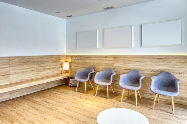 Recepción de diseño moderno con sillas grises, cuadros, paredes blancas. suelo de madera y mampara. clínica dental.