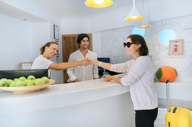 Recepción del hotel resort y registro de huéspedes. recepcionistas de hombre y mujer en el lugar de trabajo