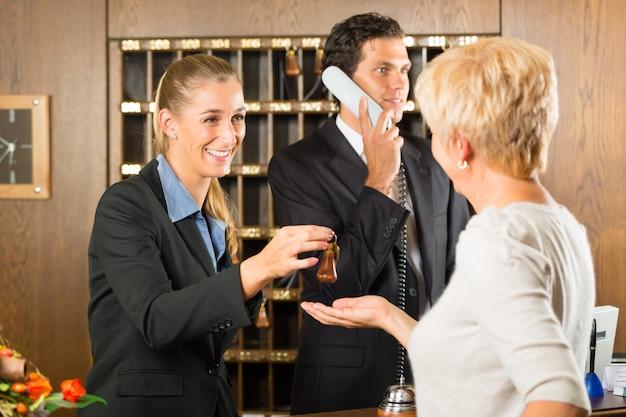 Recepción, huéspedes que se registran en un hotel