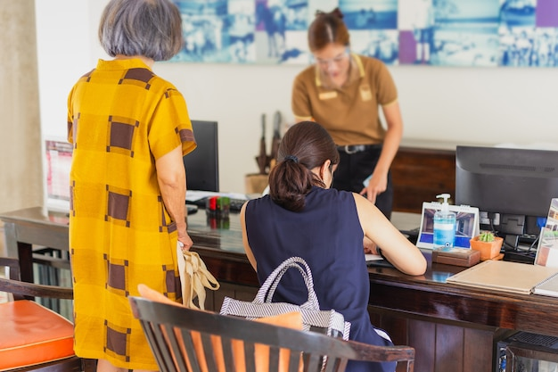 Recepción de la mujer en el hotel con careta con mujer check in en el hotel.
