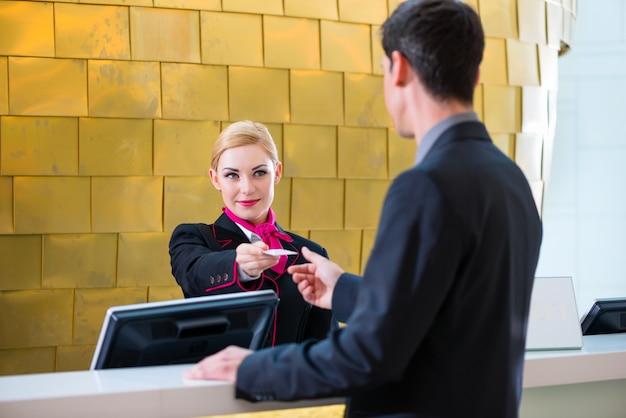 Recepción de recepcionista del hotel en el hombre dando la tarjeta llave