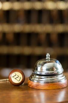 Recepción, timbre del hotel y llave en el escritorio