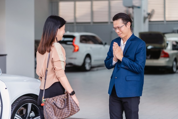 Recepcionista asiática da la bienvenida al cliente a visitar el centro de servicio de mantenimiento para revisar el automóvil en la sala de exposición