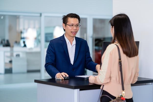 La recepcionista asiática recibió la llave automática del automóvil para verificar en el centro de servicio de mantenimiento en la sala de exposición