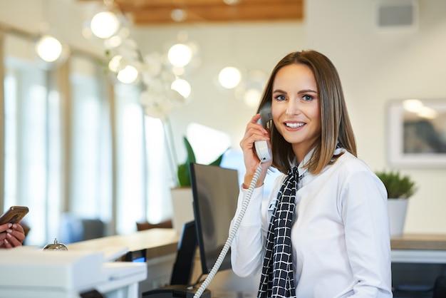 Recepcionista contestando el teléfono en la recepción del hotel.