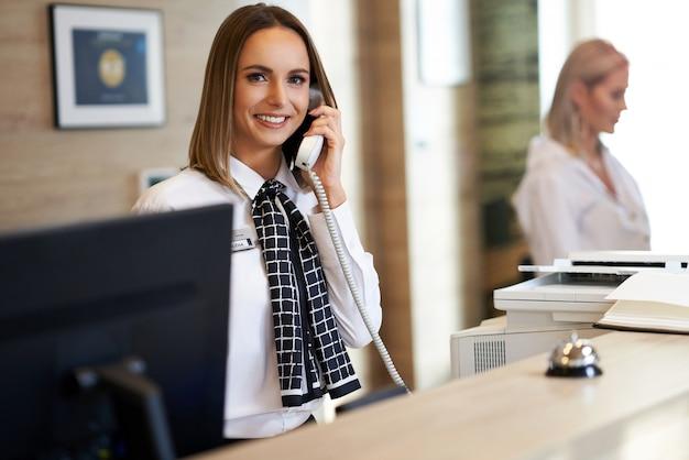 Recepcionista contestando teléfono en la recepción del hotel