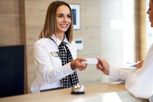 Recepcionista dando tarjeta llave a la empresaria en la recepción del hotel