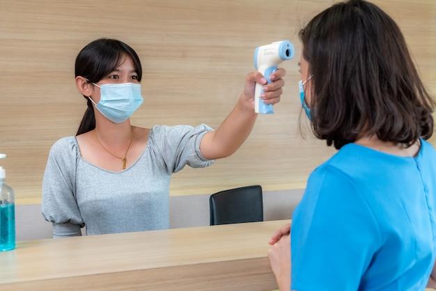 Recepcionista e invitado con mascarilla en la recepción mientras conversan en la oficina o el hospital