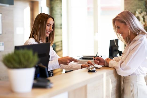 Recepcionista y empresaria en la recepción del hotel