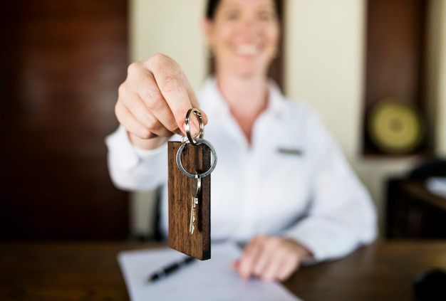 Recepcionista entregando la llave de la habitación al huésped.