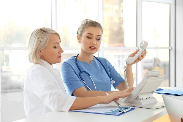 Recepcionista femenina con aprendiz en el hospital
