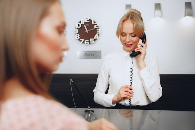Recepcionista femenina en el hotel hablando por teléfono en el trabajo de cerca
