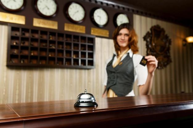 Recepcionista del hotel y mostrador con campana