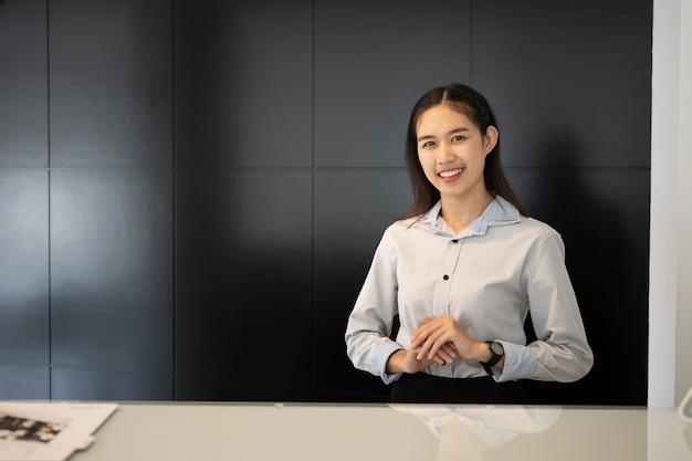 Recepcionista joven asiática de pie en el mostrador de recepción y sonriendo para dar la bienvenida a los visitantes del hotel.