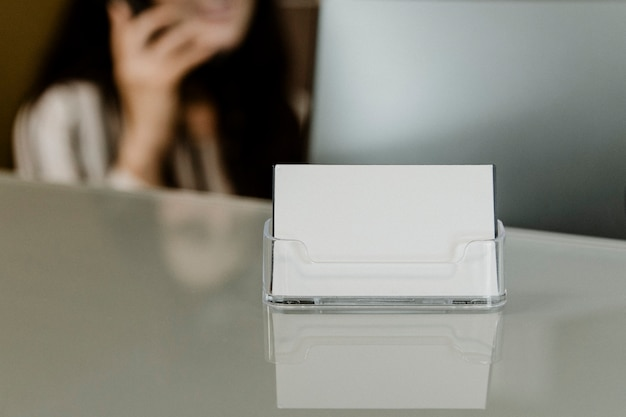 Recepcionista sentada junto a la tarjeta de presentación de la empresa