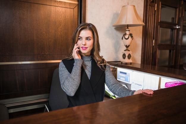 Recepcionista de sexo femenino joven que se sienta en su escritorio que habla en el teléfono móvil