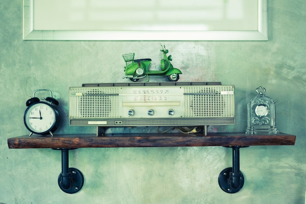 Receptor de radio de difusión retro en estante de madera con fondo de pared de hormigón.