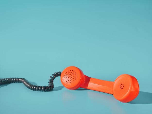 Receptor de teléfono naranja sobre fondo azul.