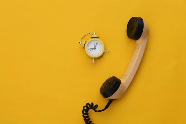 Receptor de teléfono retro y despertador sobre un fondo amarillo.